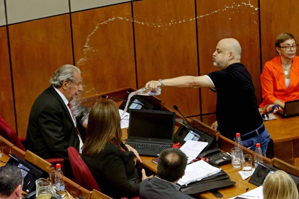 Momento en el que el exsenador arremetió con agua contra su compañero el senador Juan Carlos Galaverna, en abril de 2019. Foto: Christian Meza.