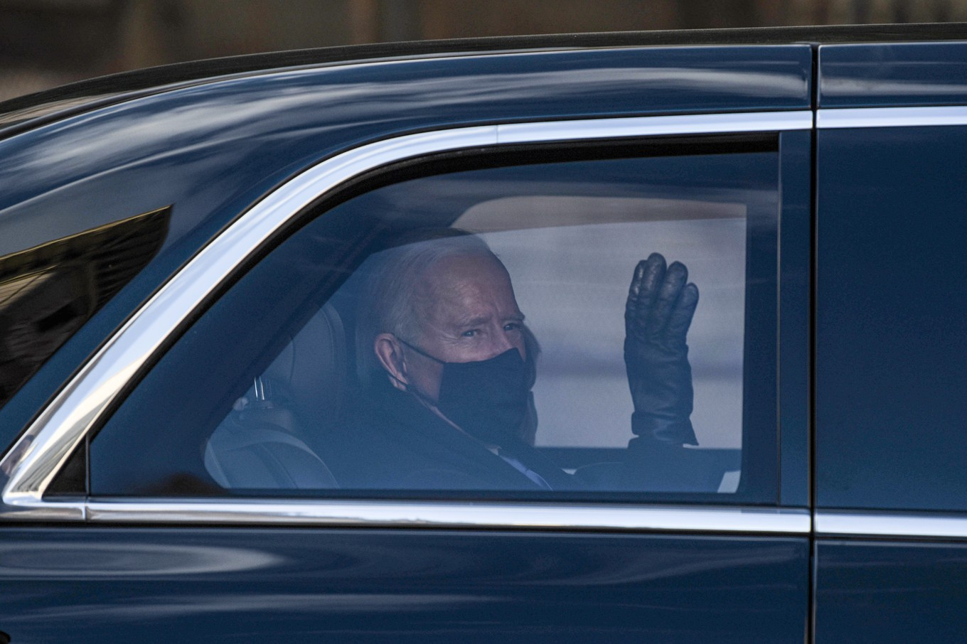 US President Joe Biden waves to supporters along the motorcade route in Washington, DC, January 20,2021after being sworn in as the 46th President of the United States. (Photo by SETH HERALD / AFP)